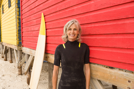 beige: Portrait of smiling senior woman standing by red hut at beach