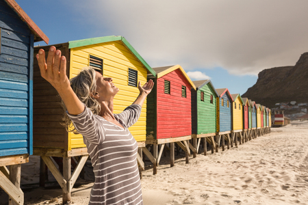 Woman with arms raised standing on sand against beach huts