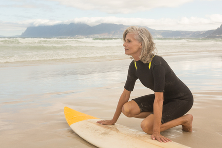 Senior woman kneeling by surfboard on shore at beach