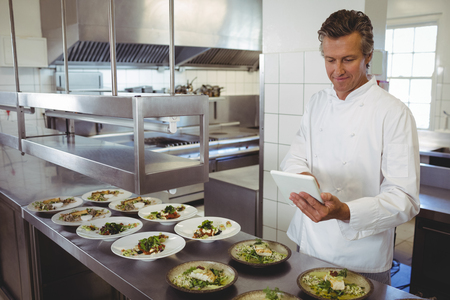 Male chef using digital tablet at order station in restaurant Foto de archivo