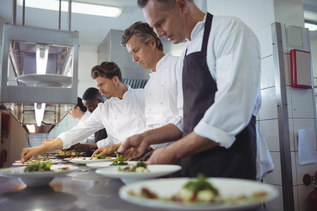 Team of chefs garnishing meal on counter in commercial kitchen Stock Photo