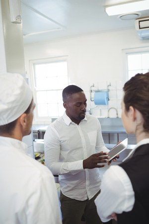 Male restaurant manager using digital tablet while briefing to his kitchen staff in the commercial kitchen