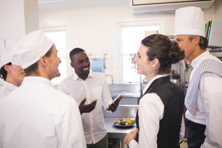 業務用厨房の彼のキッチンのスタッフに説明会男性店長 写真素材