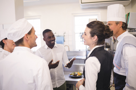 Male restaurant manager briefing to his kitchen staff in the commercial kitchen