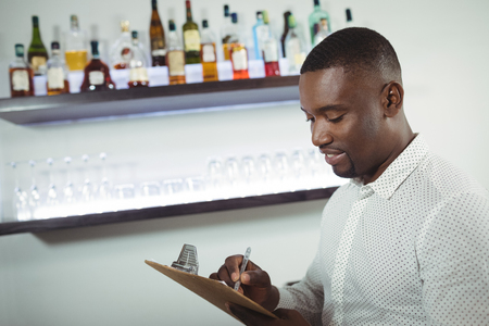 Bar tender writing on a clipboard at bar counter in restaurant