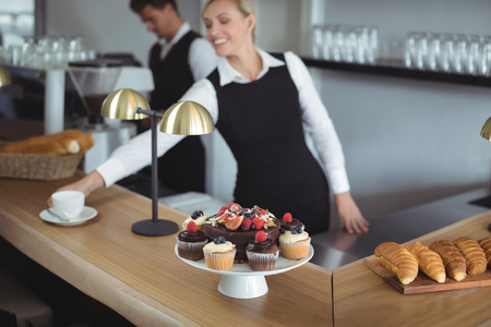 Waitress serving coffee at counter in restaurant