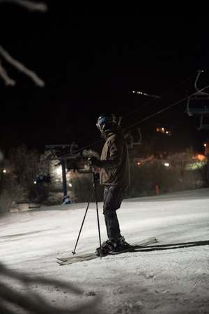 Skier skiing in snowy alps at night