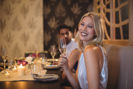 Portrait of smiling beautiful woman with champagne glass in restaurant