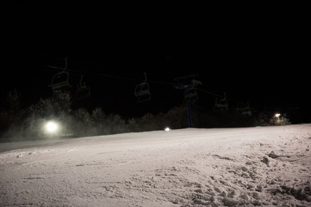 Empty ski lift over snowy landscape at night