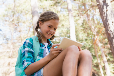 Smiling girl using a digital tablet in the forest on a sunny day