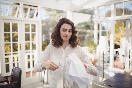 Beautiful waitress cleaning wine glass with napkin in restaurant Stock Photo