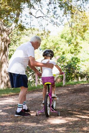祖父孫娘森で自転車の乗り方を教える 写真素材