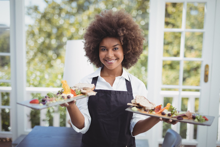 Portrait of smiling waitress holding food tray in restaurant