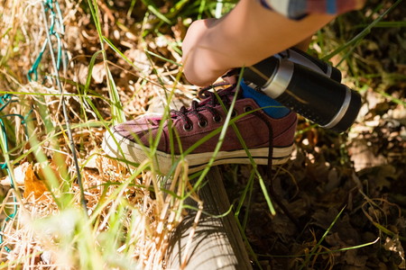 Close-up of boy tying shoelace in the forest Stock Photo