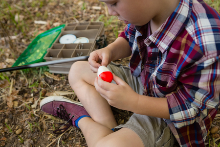 Close-up of boy preparing a bait in the forest
