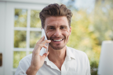 Portrait of handsome man talking on mobile phone in restaurant Stock Photo