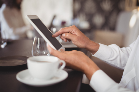 Mid section of woman using digital tablet in restaurant
