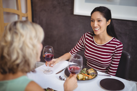 Two women interacting with each other while having wine in restaurant