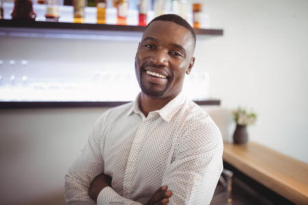 Portrait of man standing with arms crossed in restaurant