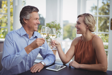 Smiling couple toasting glasses of wine in restaurant