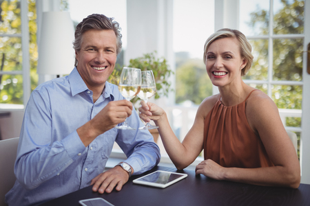 Portrait of smiling couple toasting glasses of wine in restaurant Stock Photo