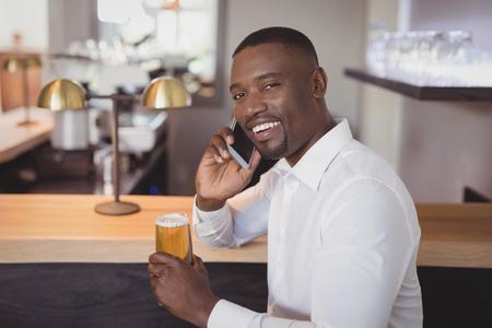 Man talking on mobile phone while having beer in restaurant