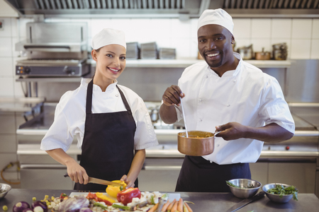 Chefs preparing food in the commercial kitchen at restaurant Stock Photo