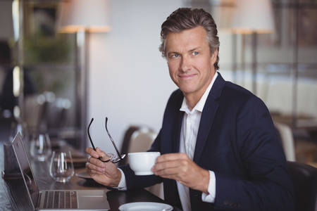 Smiling businessman having coffee in restaurant Stock Photo