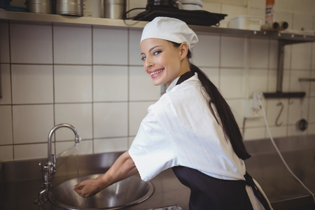 Female chef washing hands in the commercial kitchen at restaurant