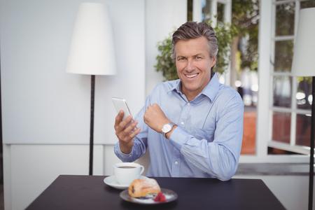 Portrait of businessman using mobile phone in restaurant Stock Photo
