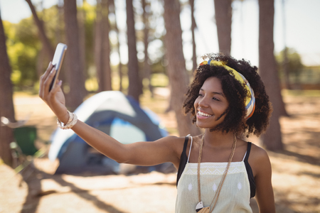 Smiling woman clicking selfie while standing against tent in forest