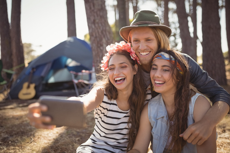Happy friends clicking selfie while camping in forest on sunny day Stock Photo