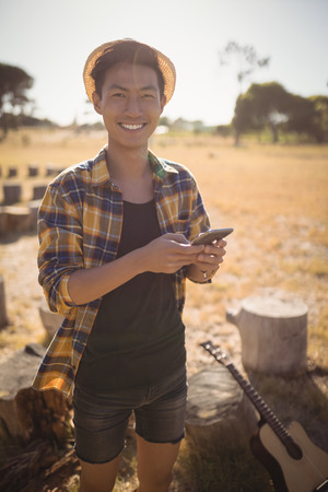 Portrait of smiling man using mobile phone while standing on field Stock Photo