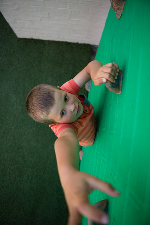 High angle view of boy reaching at climbing holds on green wall