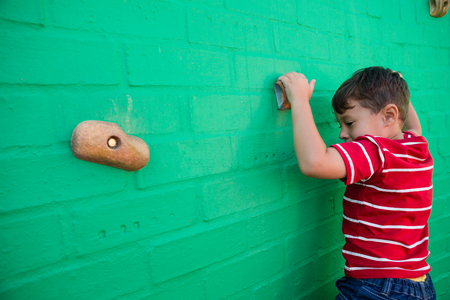 conquering adversity: Rear view of boy climbing wall at playground in school Stock Photo