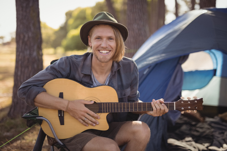 Portrait of smiling young man playing guitar while sitting on chair by tent at forest