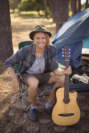 Portrait of smiling young man holding guitar while sitting on chair by tent at forest