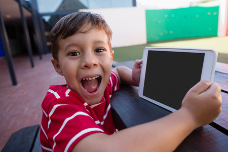 Portrait of cute boy holding digital tablet while sitting at table in school Stock Photo