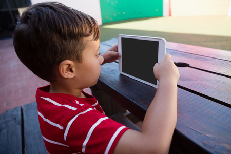 Side view of cute boy holding digital tablet while sitting at table in school Stock Photo