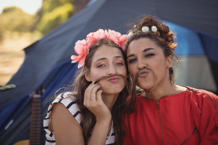 Close up portrait of young female friends against tent