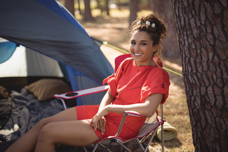 Portrait of smiling young woman sitting on chair by tent at forest