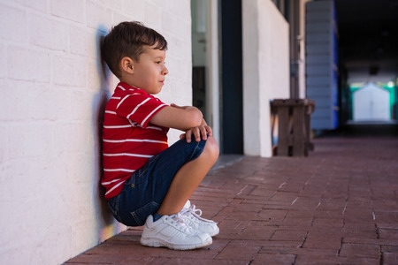 Side view of boy crouching by wall in school building Stock Photo