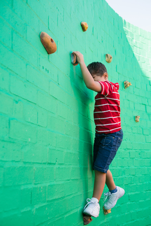 Cute boy climbing wall at playground in school