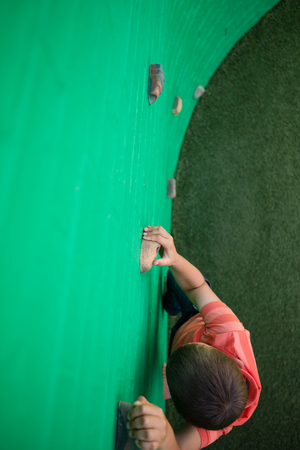 Overhead view of boy climbing on green wall Stock Photo