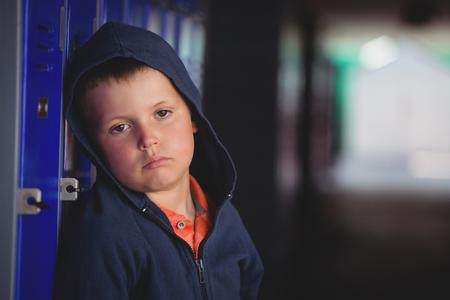 Portrait of sad boy leaning on locker at school