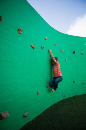 Full length of boy climbing on green wall against sky Stock Photo