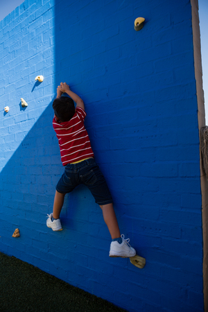 Rear view of boy climbing blue wall at playground in school Stock Photo