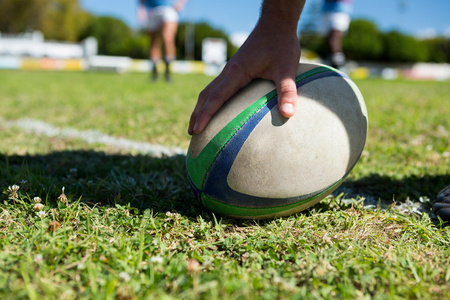 Cropped image of player touching rugby ball at field