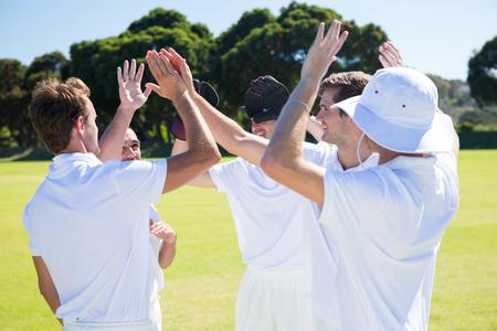 晴れた空に対してフィールドで勝利を祝って笑顔のクリケット選手