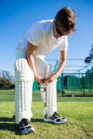 Cricket player wearing kneepad while standing on grassy field against clear sky